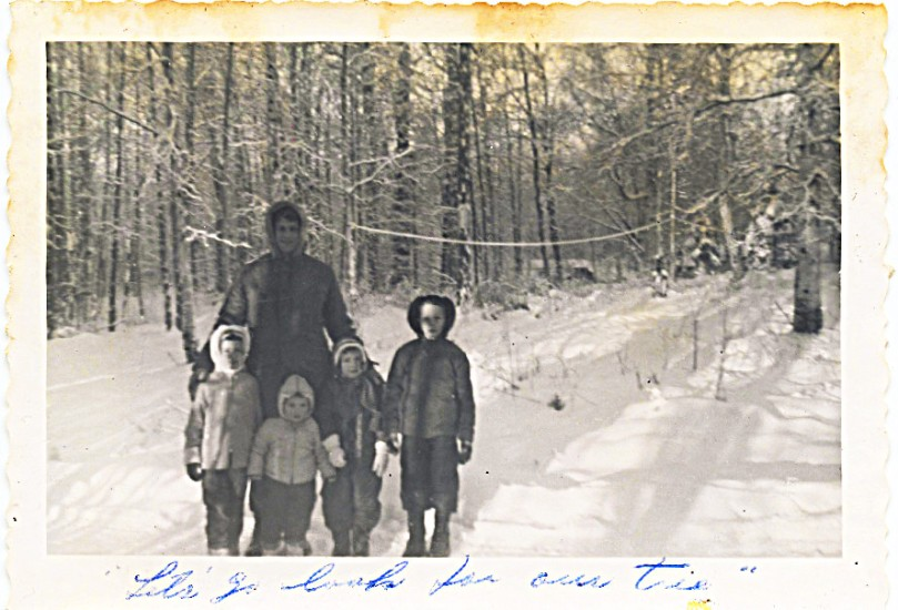 Here I am with family at log house December 1957, 6 years old -- why I'm not in pictures of tree coming into house, I don't know, but I AM here!