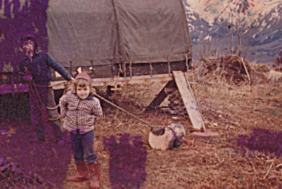 1959 - Sharon and the Jamesway hut - John about lost in the fire damage to this photo, hauling a chunk of firewood with a rope