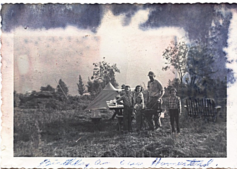"1959 July -Mother:  ""Birthday on our Homestead"" - on back:  ""The clouds obliterated the mountains in back-ground.  This was about 7:00 in the evening"" -- Probably Sharon's 4th birthday - I'm the one standing alone to my father's left - amazing for all the fire and water damage that the5 of us were so nicely preserved!"