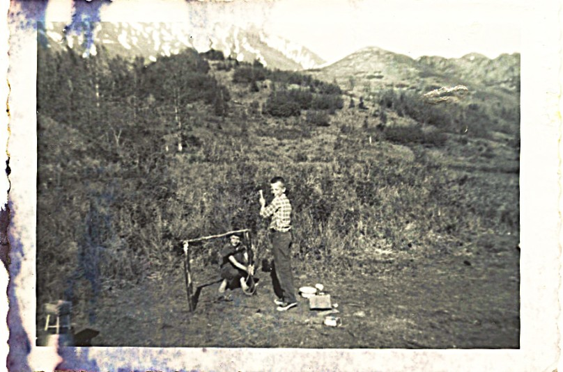 "1959 - John and Linda - mother says on back of photo:  ""This shows the small hill beyond (behind) our hut -- note scrubby bushes.  See the high mountain region still covered by snow way behind us.  Very beautiful in color.  John and Linda were making foundation for a tent."""