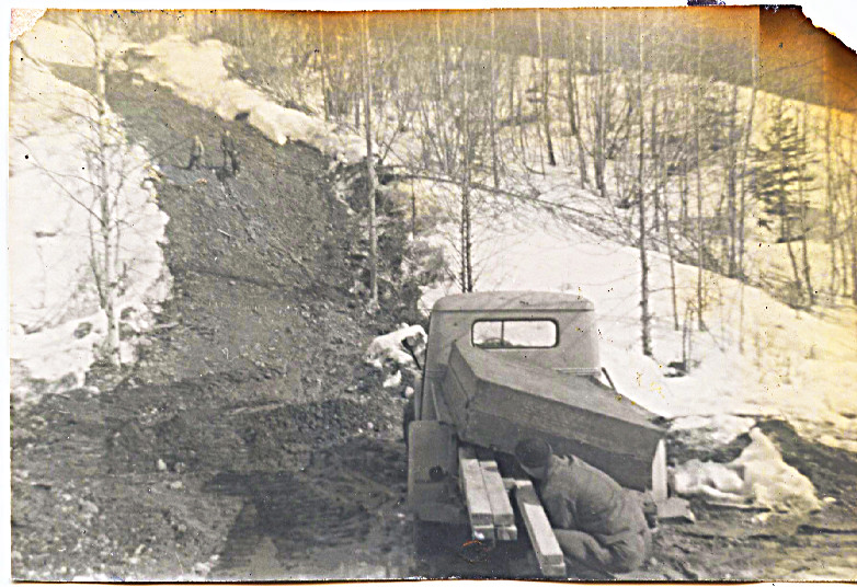 1959 Dad checking Jamesway flooring load in back of Jeep truck before hooked to tractor to get dragged up Horror Hill