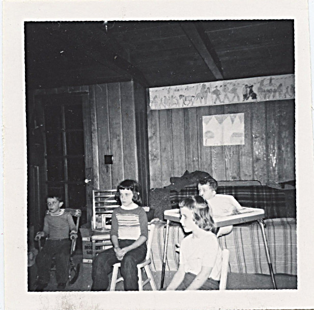 "1962 - log house, David in baby butler, Sharon, Cindy and ""customer"" in the Happy Time Nursery"